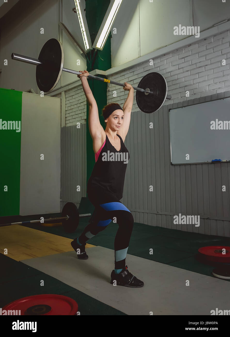Mujer fuerte levantamiento barbell como parte de crossfit la rutina de ejercicios. Imagen De Stock