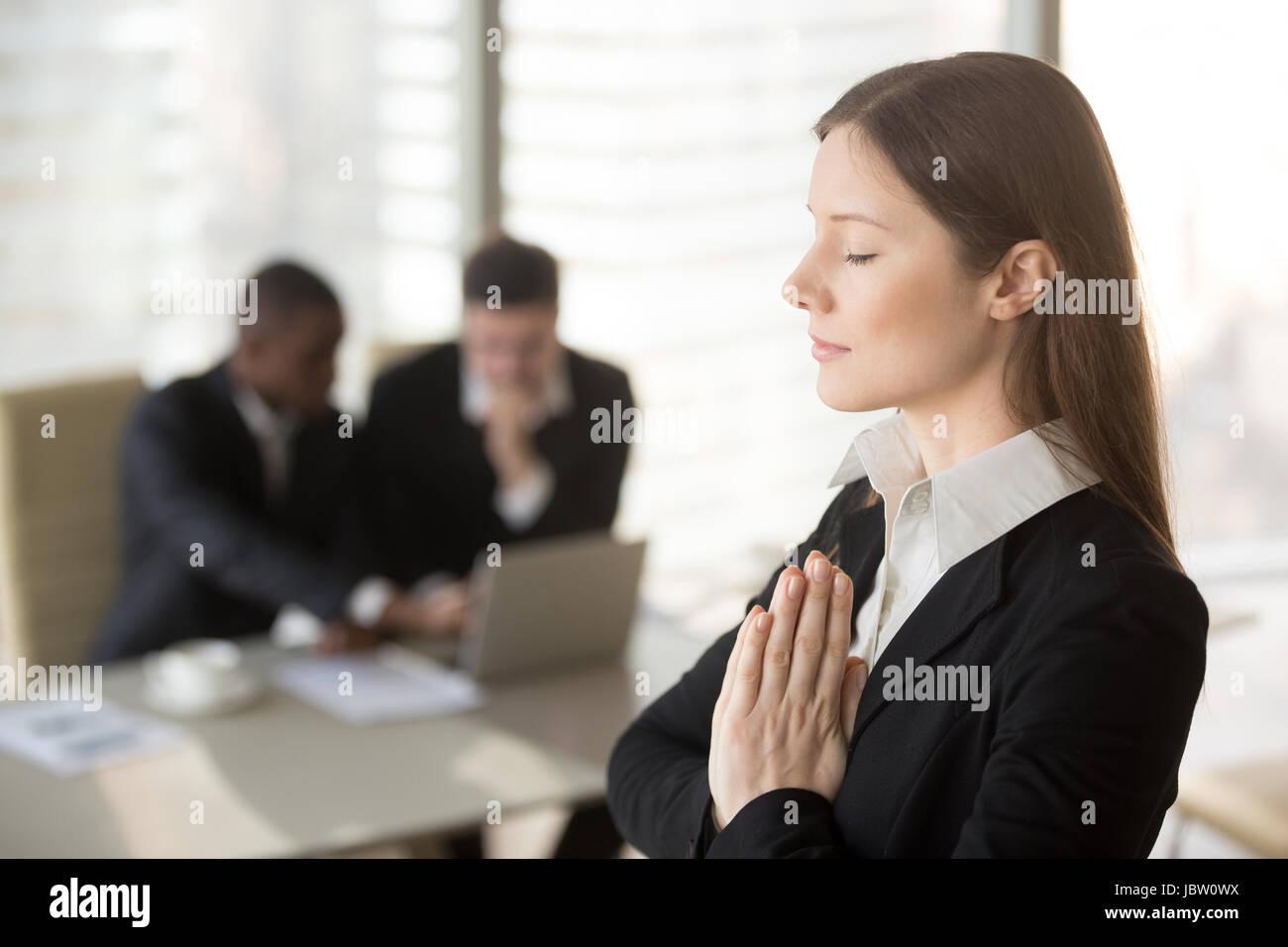 Hermosa joven empresaria goza de meditar en la oficina permanente con los ojos cerrados, poner las manos juntas Imagen De Stock
