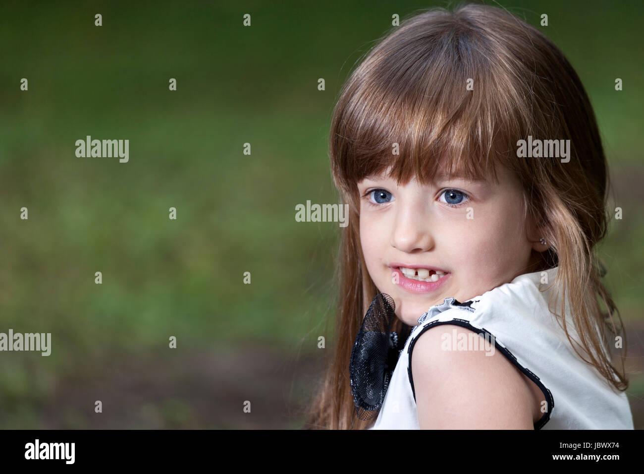Retrato de una linda niña con grandes ojos azules en el parque Imagen De  Stock d4ae7b9f472