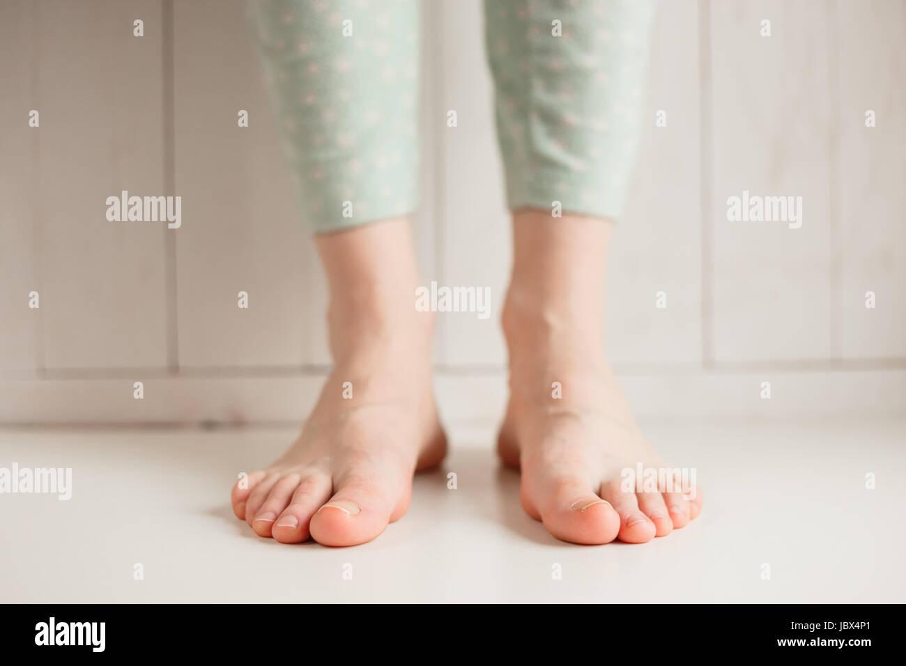 Los pies descalzos de una chica cansada de zapatos incómodos, cerca. Foto de stock