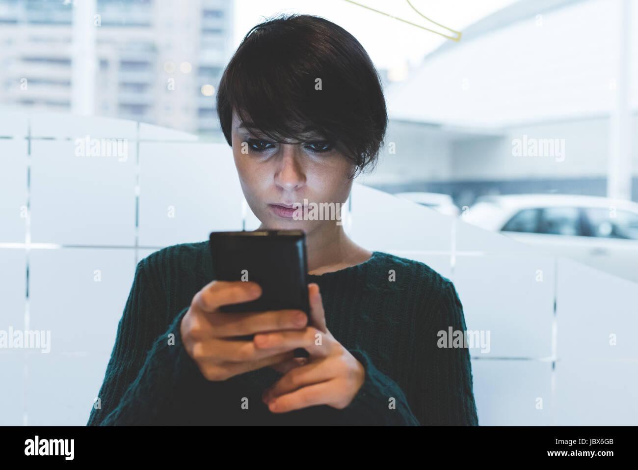 Mujer en el café mirando el smartphone Imagen De Stock