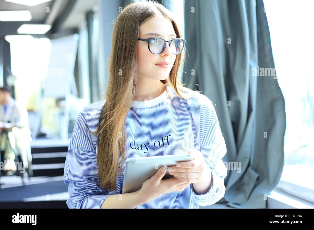 Atractiva empresaria trabajando en una tableta digital en la oficina Imagen De Stock