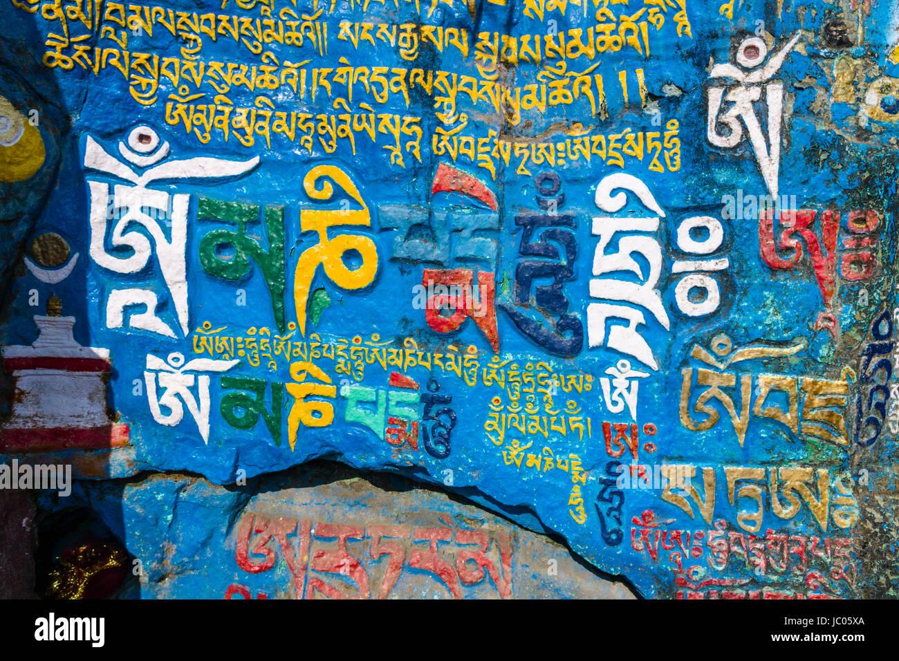 El tibetano mantra om mani padme hum está excavada en una roca y pintado de colores vivos Imagen De Stock