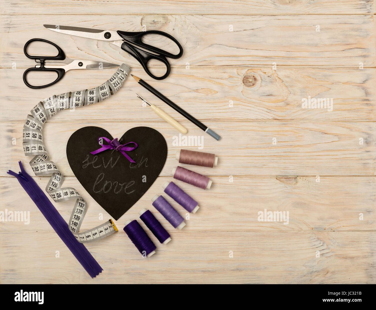 Accesorios de costura de color púrpura y el corazón con una inscripción - coser en el amor. El enfoque selectivo. Foto de stock