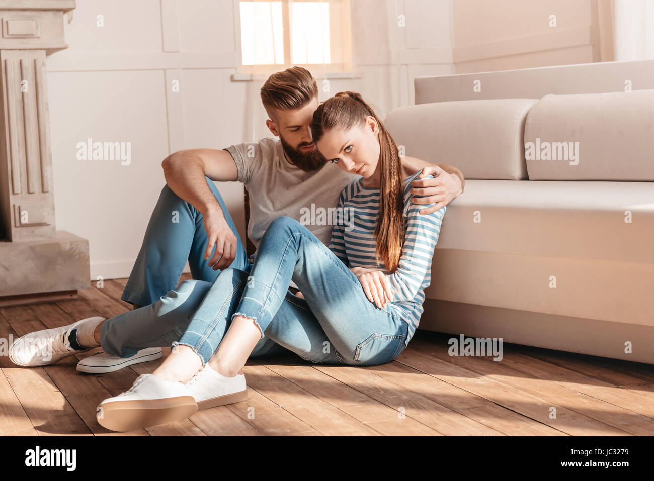 Licitación joven hombre y mujer abrazar y sentarse en el suelo en casa Imagen De Stock