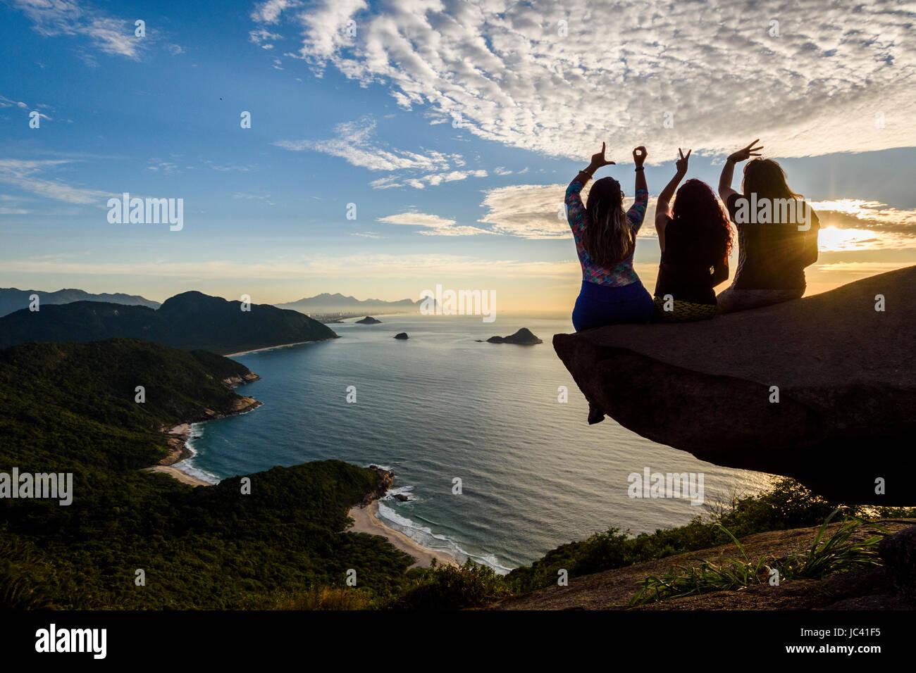 La mujer en el borde de la montaña en Pedra do Telégrafo deletrear el amor con sus dedos, Río Imagen De Stock