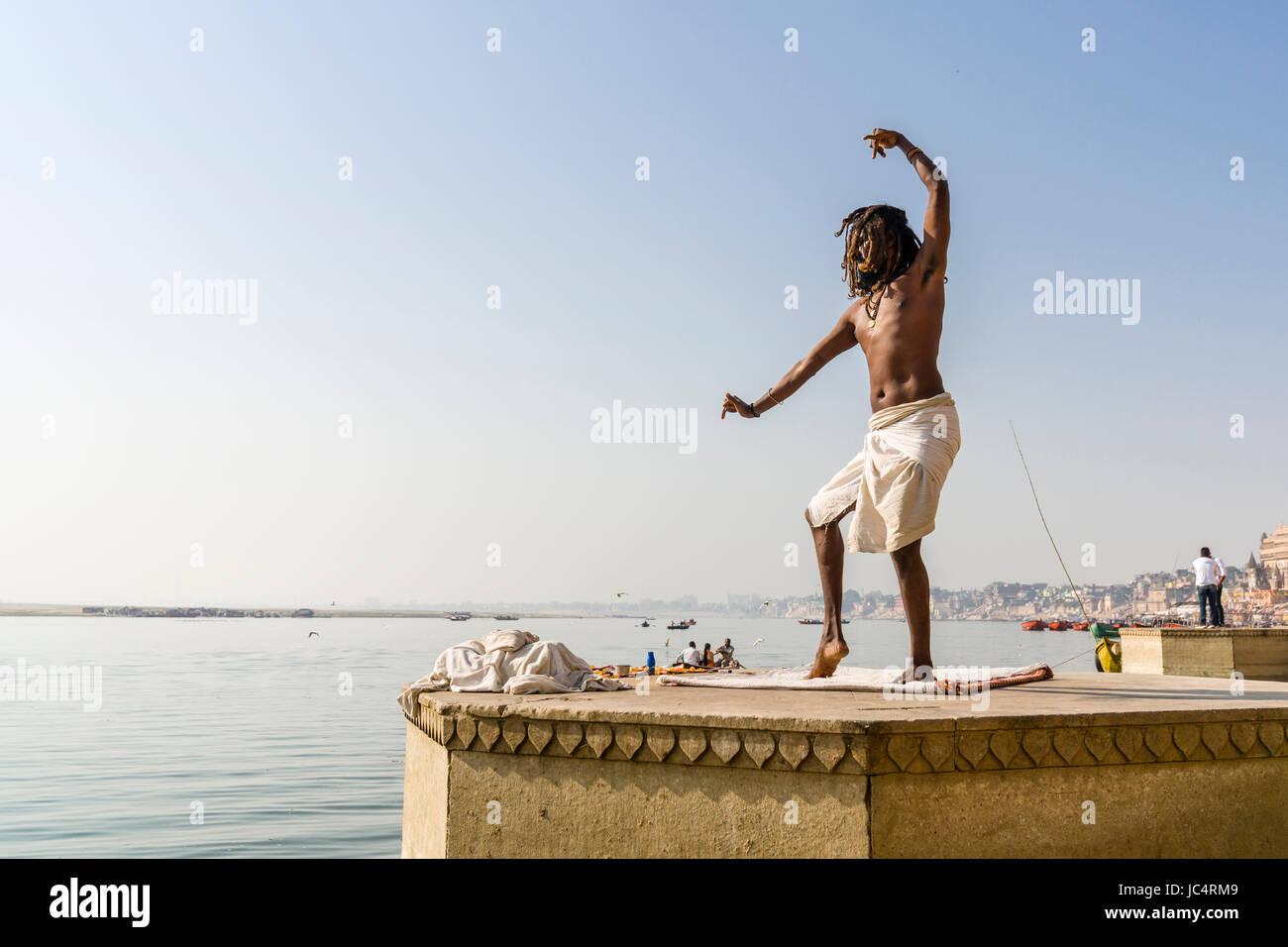Un sadhu, hombre santo, baila sobre una plataforma en el río santo Ganges en meer ghat en el suburbio godowlia Imagen De Stock