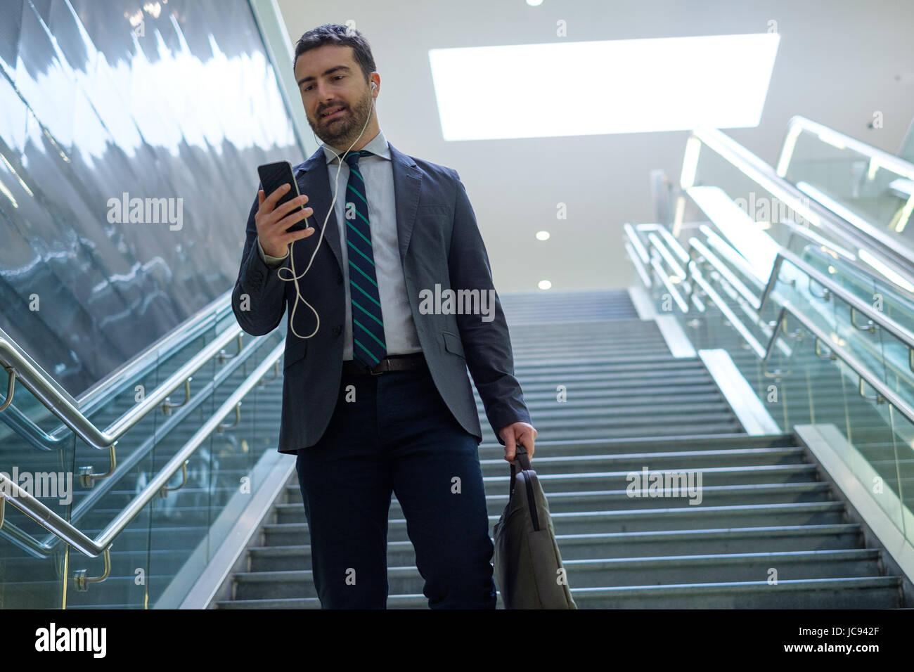 El empresario está mirando su teléfono móvil mientras va a trabajar Imagen De Stock