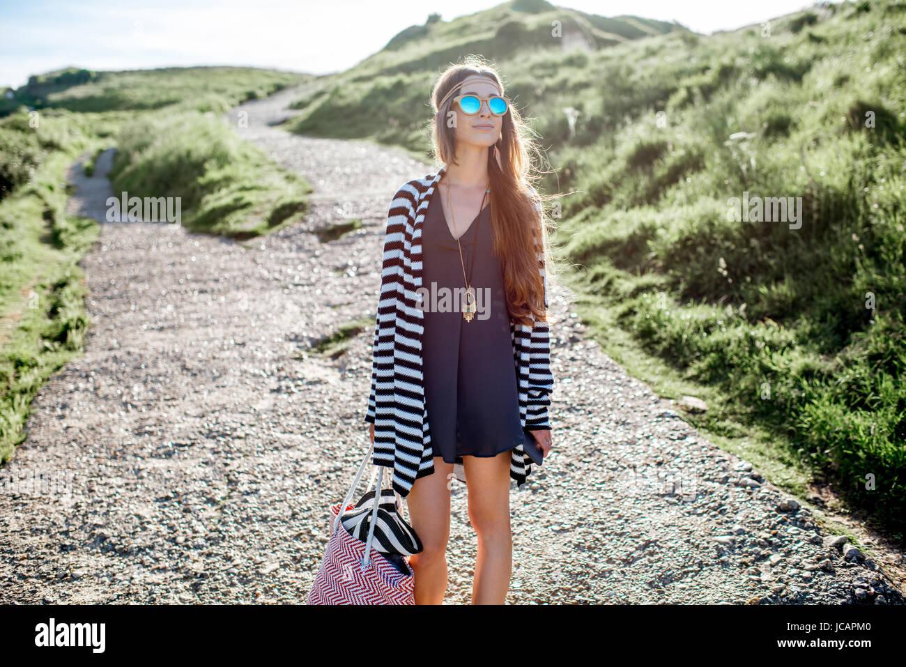 c66d6e004c52b Muchacha vestida en estilo hippie caminando con bolsa de playa al aire  libre Imagen De Stock