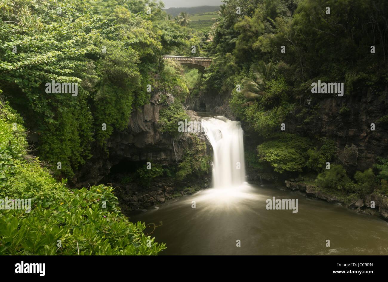 Cascada bajo el puente de carretera en siete piscinas sagradas Maui Foto de stock