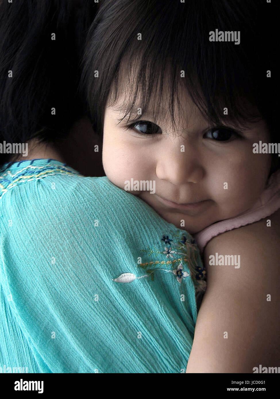 Poco niño hispano mostrando su sonrisa mientras mantiene su madre Imagen De Stock