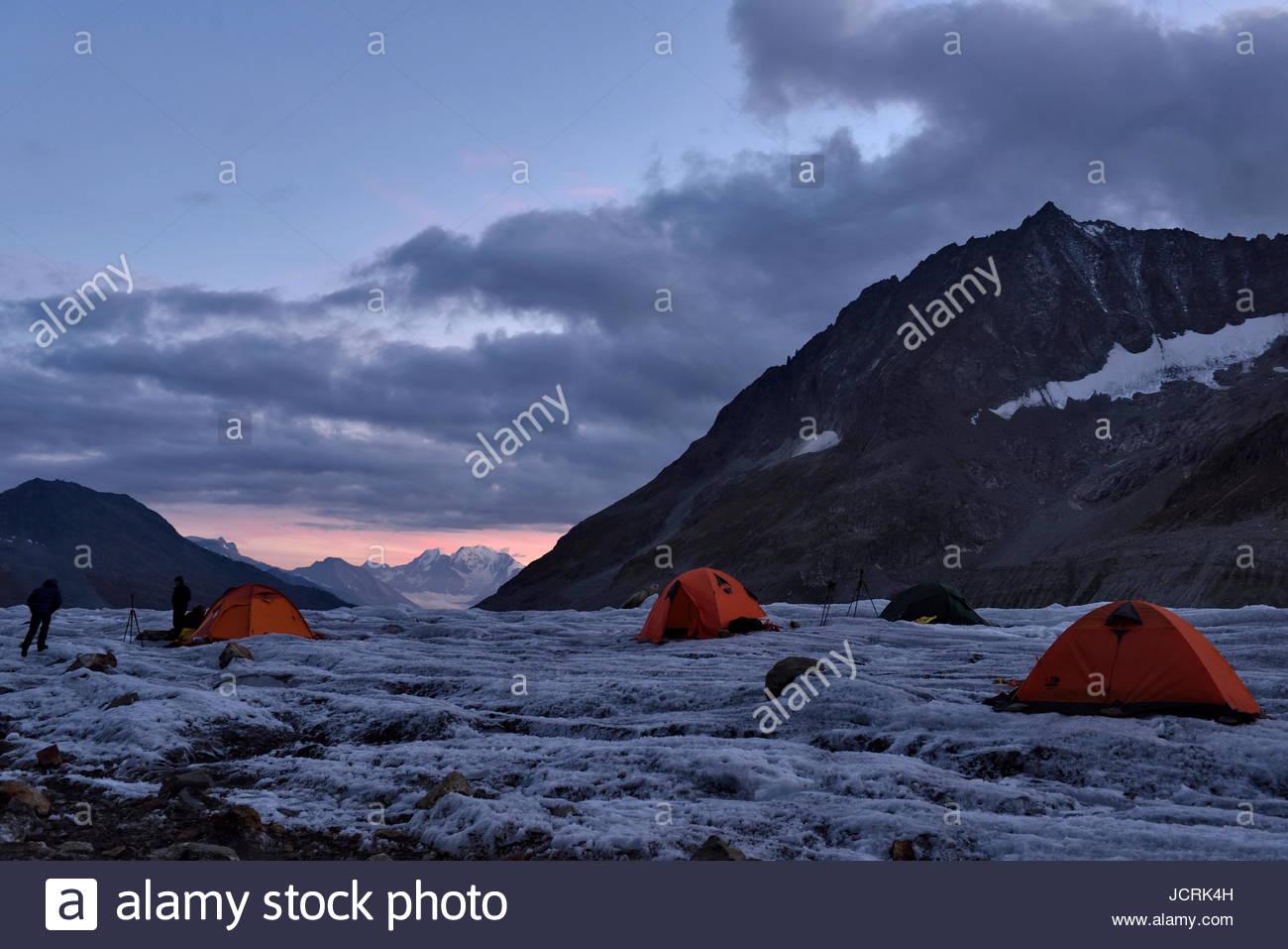 El equipo de espeleólogos italianos asentarse en la noche en su campamento base en el Aletschgletscher. Crepúsculo Imagen De Stock