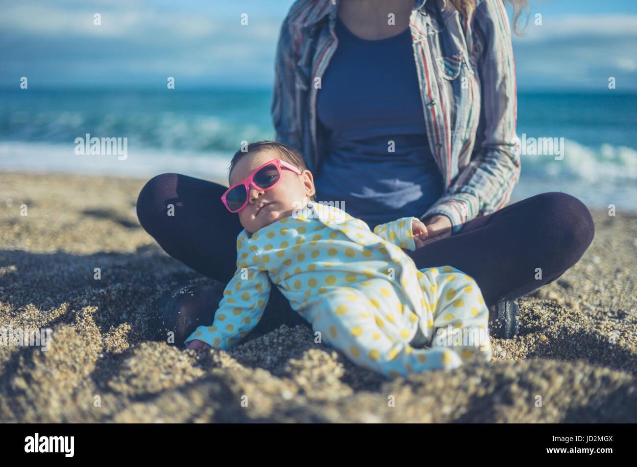 Un bebé es fresco con gafas de sol y relajándose en la playa con su madre Imagen De Stock