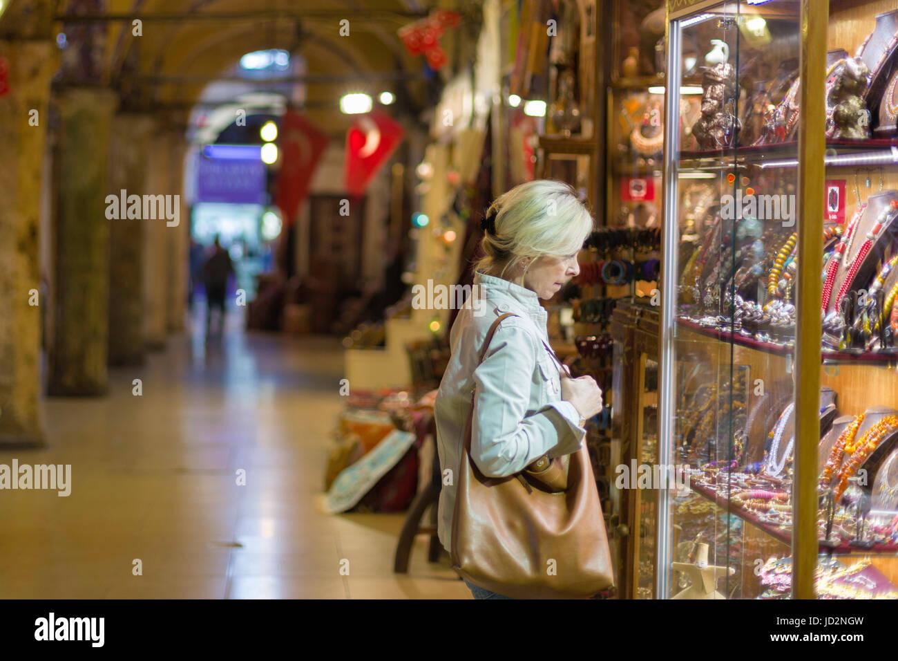 Mujer de mediana edad en escaparate de compras en el Gran Bazar de Estambul, Imagen De Stock