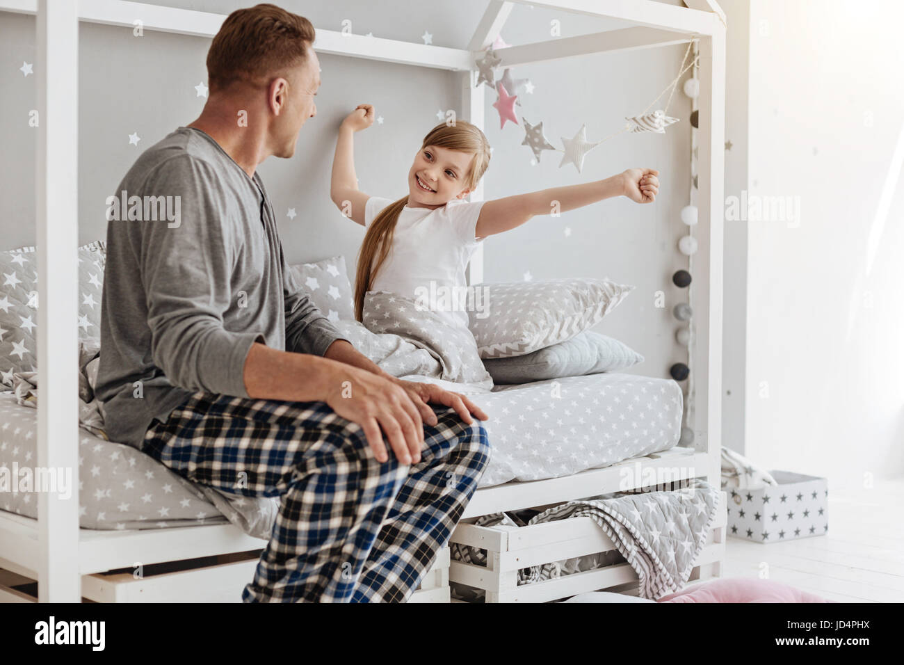 Admirable niño activo estiramiento en su cama Imagen De Stock
