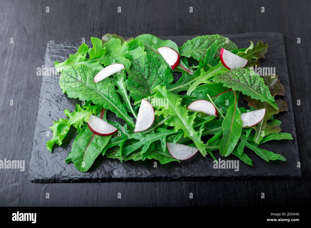 Ensalada mixta con hojas de rábano negro placa de pizarra. Closae arriba Foto de stock