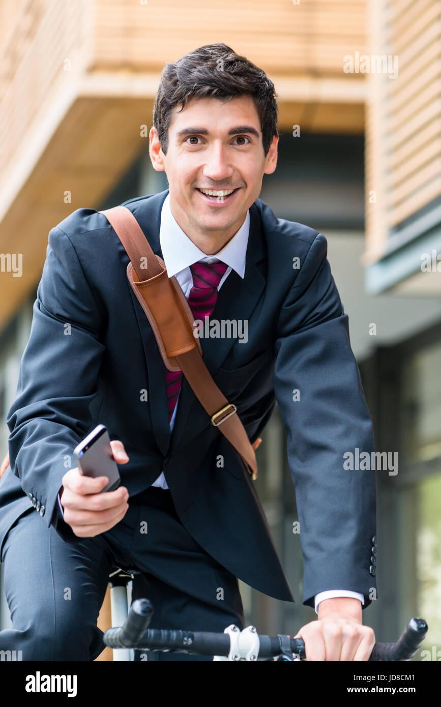 Seguro joven empresario multitarea utilizando un teléfono móvil mientras monta en bicicleta al trabajo Foto de stock