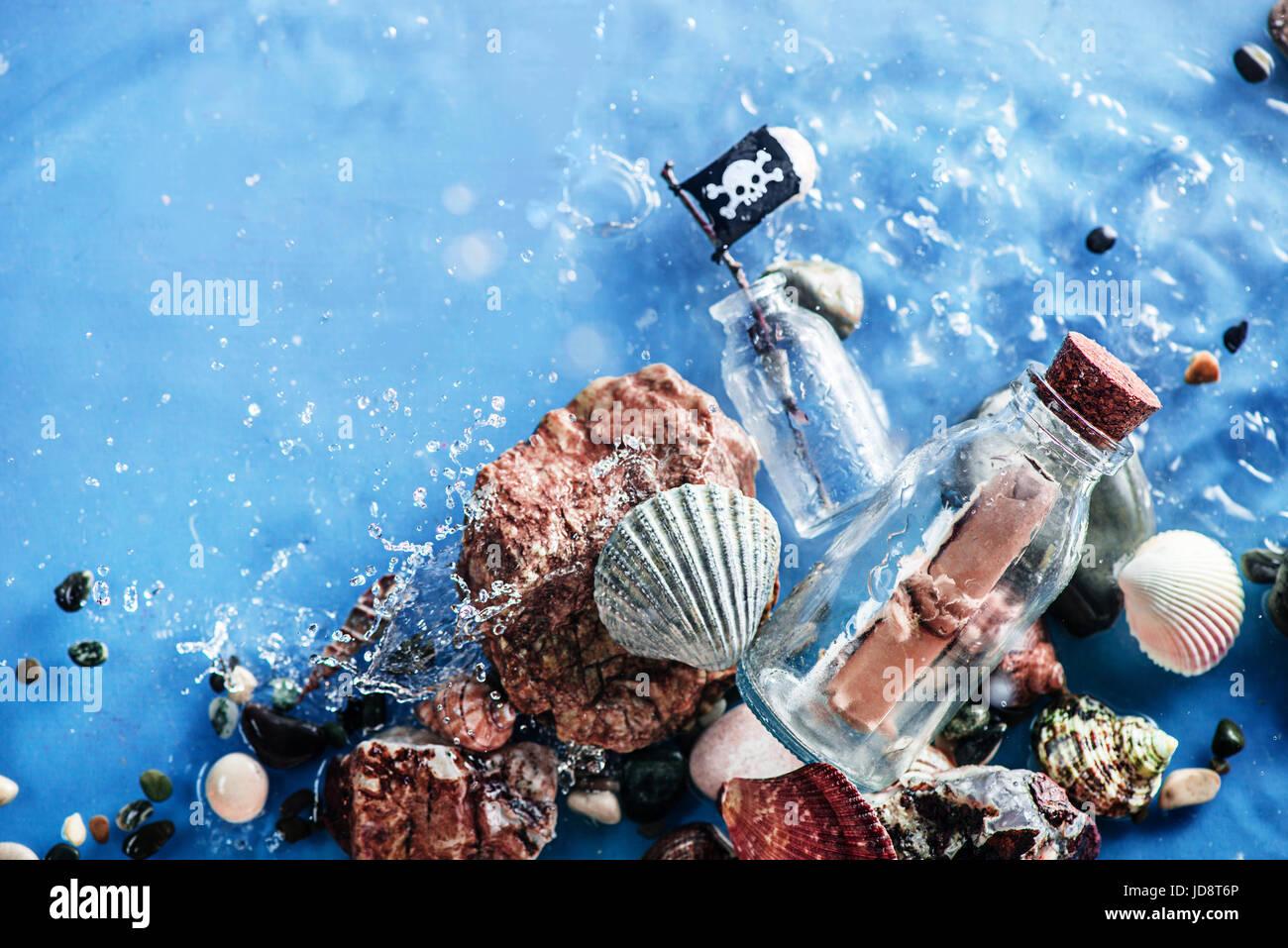 Mensaje pirata en una botella de vidrio en aguas poco profundas con rizado de seawave. todavía la vida submarina. Foto de stock