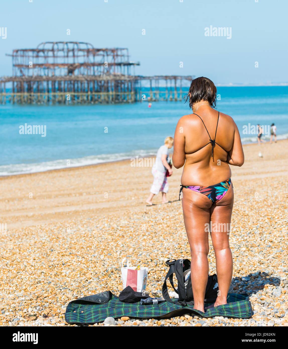 Concepto de verano. muy curtida mujer en bikini de pie en la playa en los calurosos días de verano en Brighton, Imagen De Stock