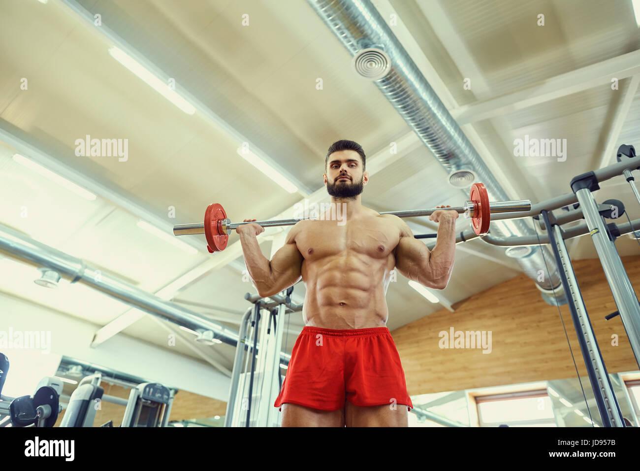 Con un culturista barbell hace ejercicios en el gimnasio. Imagen De Stock