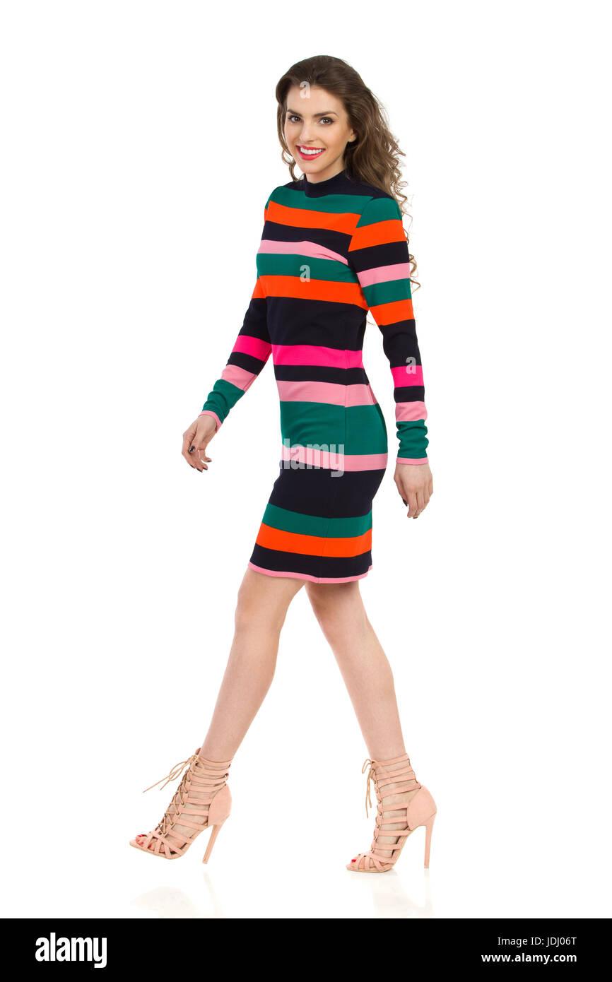 8507f74837 Modelo de moda sonriente rayas coloridas mini vestido y tacones altos está  caminando y mirando a