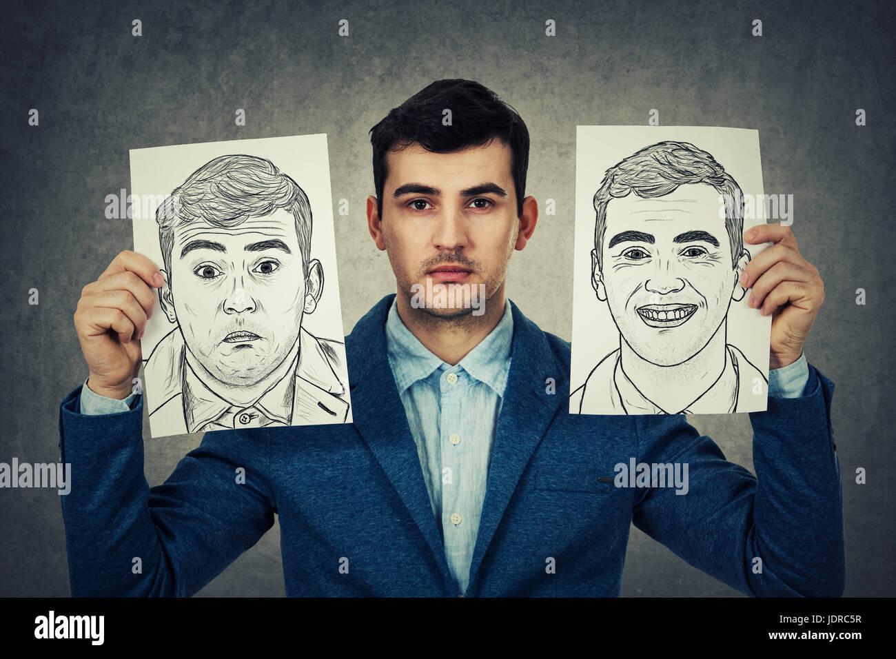 Pisado el empresario sosteniendo dos white papers con diferentes emociones dibujado. Cambiar su máscara entre Imagen De Stock