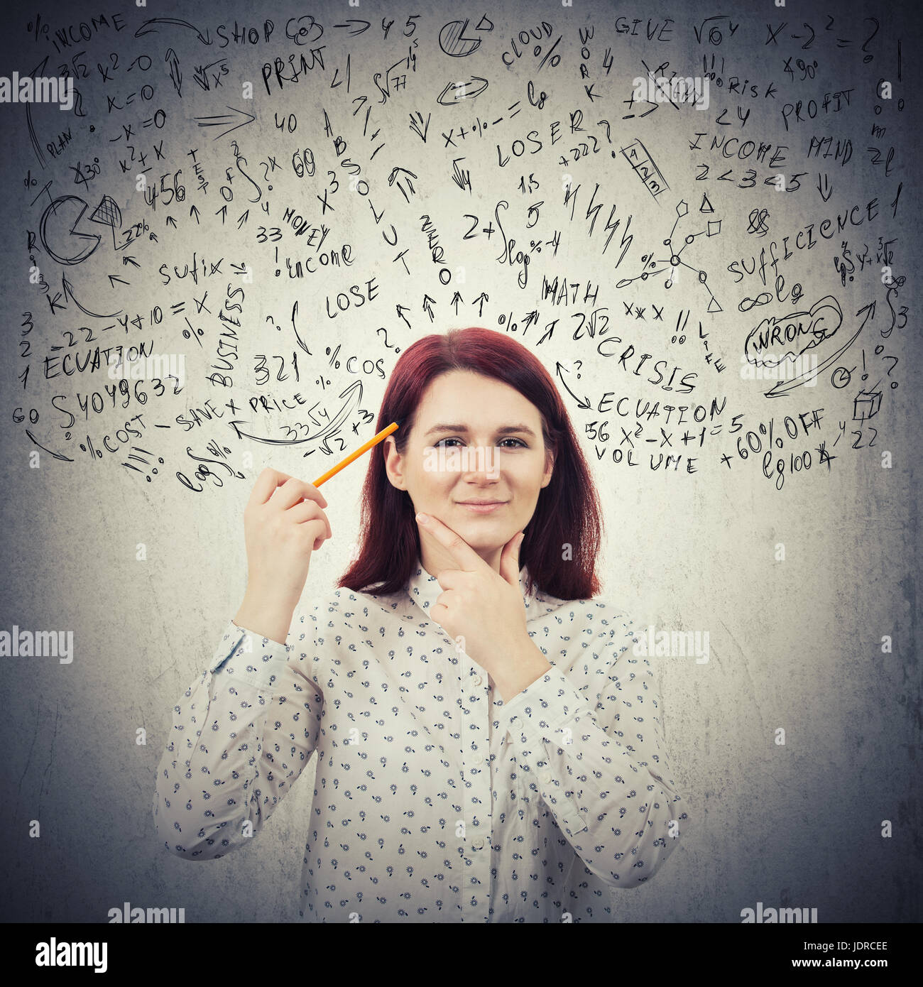 Retrato de joven, sonriente, perplejo empresaria, sosteniendo un lápiz a su cabeza creando nuevas ideas aislado Imagen De Stock