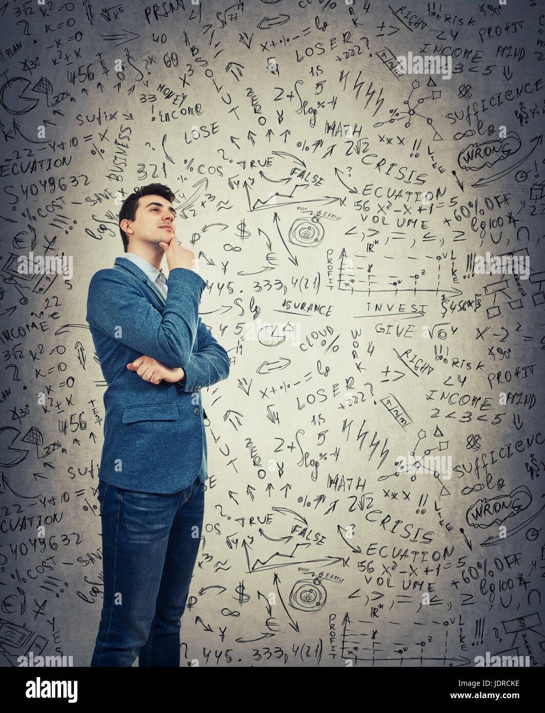 Longitud total retrato de un joven empresario con una mirada pensativa aislado sobre la pared gris de fondo. Tener Imagen De Stock