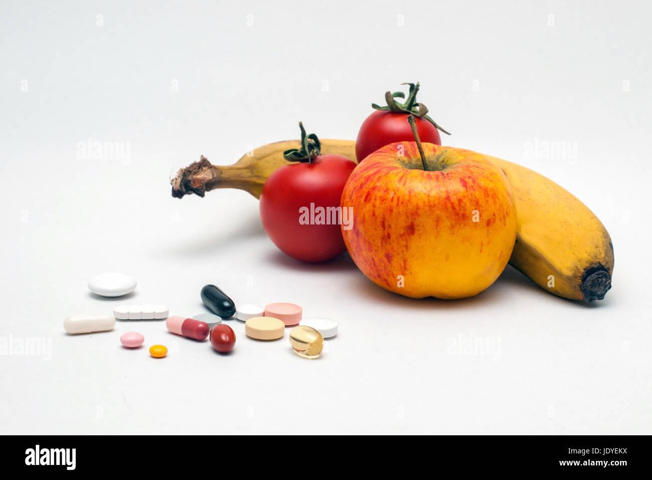 Bunte verschiedene Tabletten, Apfel, Banane und Tomaten, isoliert Foto de stock