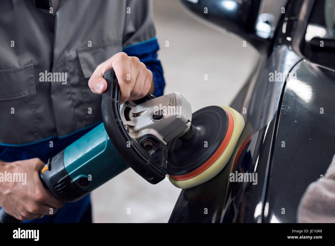 Close-up de manos con abrillantador de trabajador polaco un automóvil negro cuerpo en el taller Foto de stock