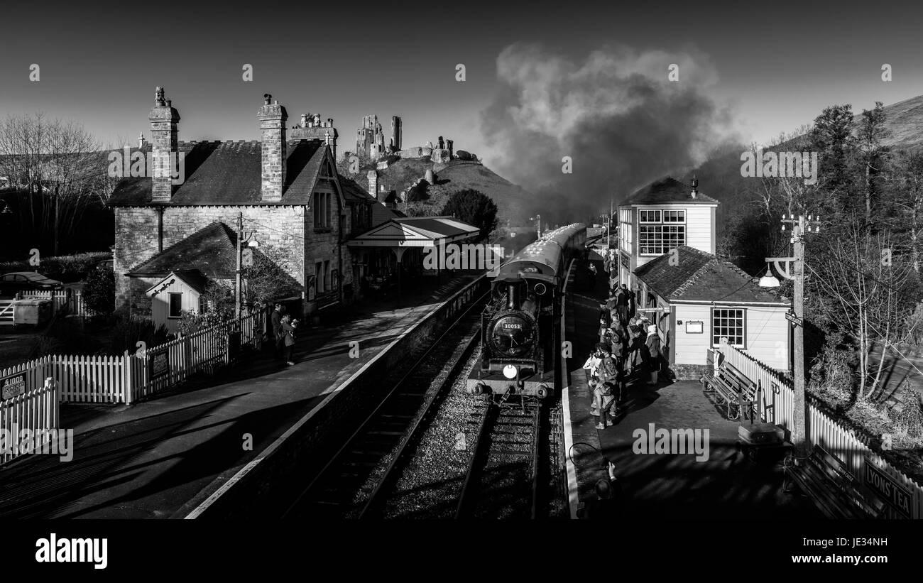 La imagen en blanco y negro de un tren a vapor en Swanage railway tomando a los pasajeros en la estación de tren el castillo Corfe, en Dorset, Reino Unido. Foto de stock