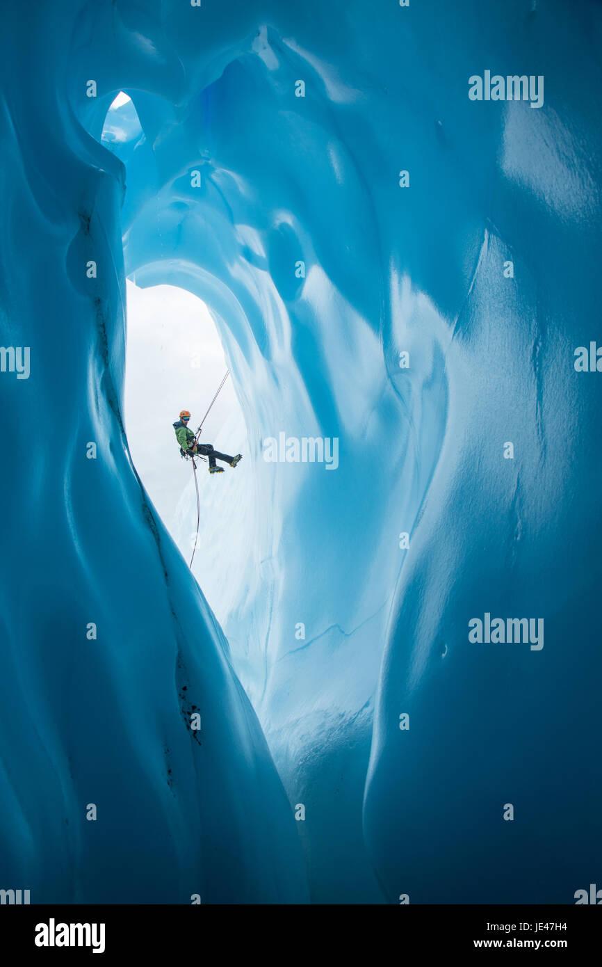 Un escalador de hielo en una chaqueta verde y naranja casco rappeles pasado una entrada grande redondeada a una cueva de hielo en el Glaciar Matanuska en Alaska. Foto de stock