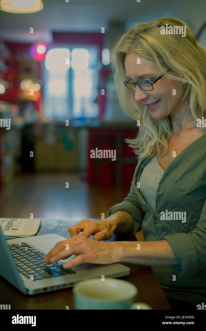 Mujer madura utilizando equipo portátil en casa Imagen De Stock