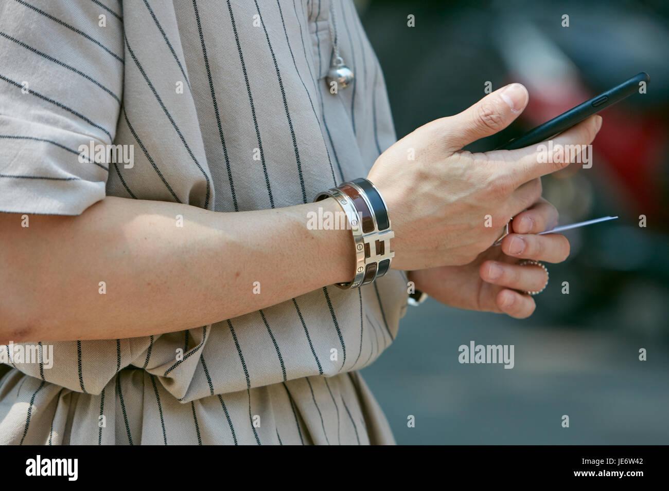 59fc2652cc32 Milán - 17 DE JUNIO  Hombre con Hermes y Cartier pulseras y smartphone  antes de Emporio Armani Fashion Show