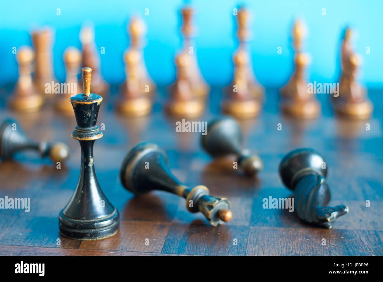 Antiguas piezas de ajedrez de madera en un viejo tablero de ajedrez. Sobre un fondo azul. Foto de stock