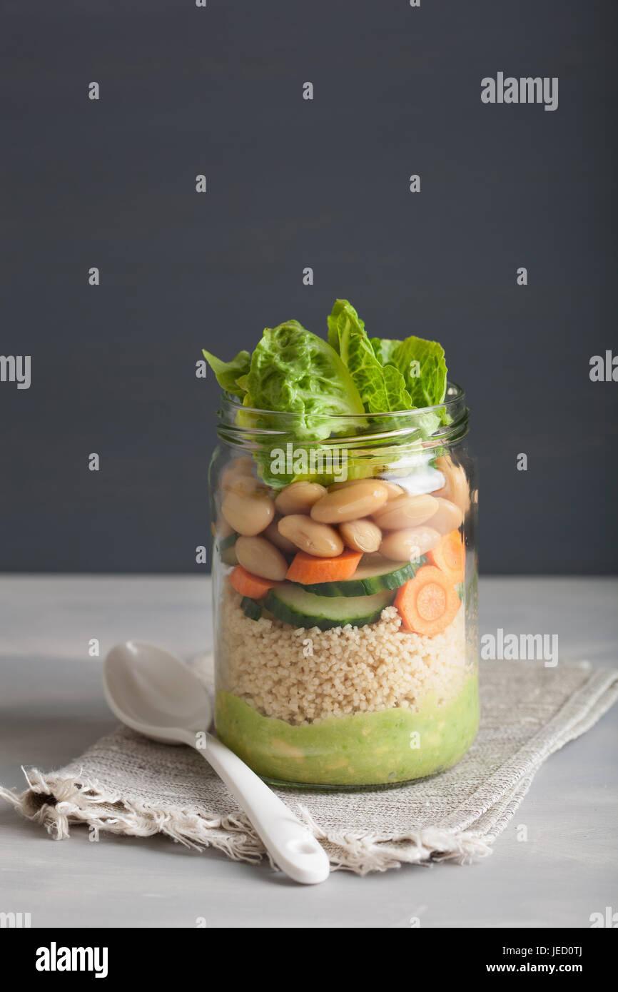Vegan cuscús ensalada en mason jar con frijoles zanahoria pepino y aderezo de aguacate Imagen De Stock