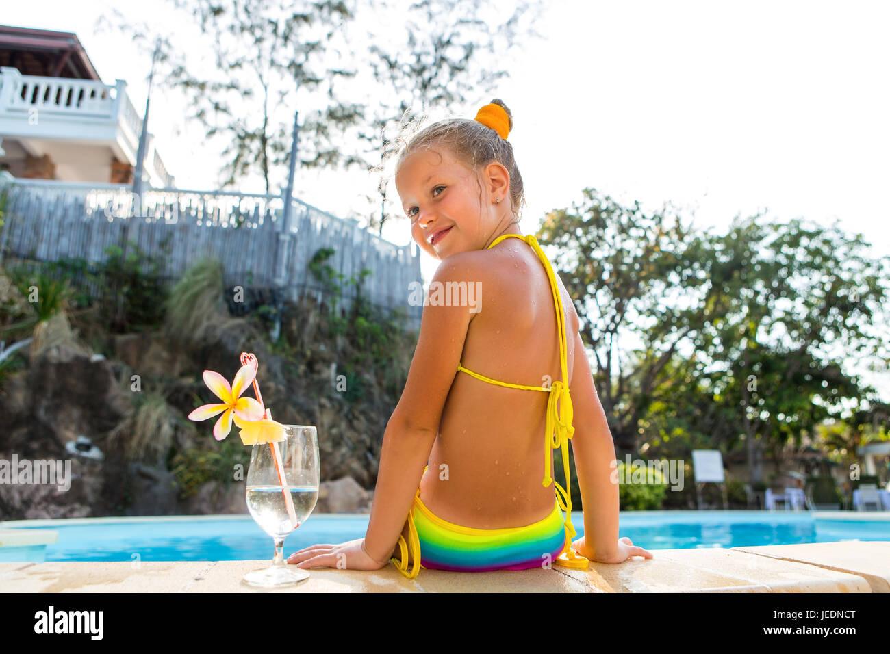 bb5d0531 Poco lindo rubia nadando en la gran piscina. Vaso grande con agua, paja y