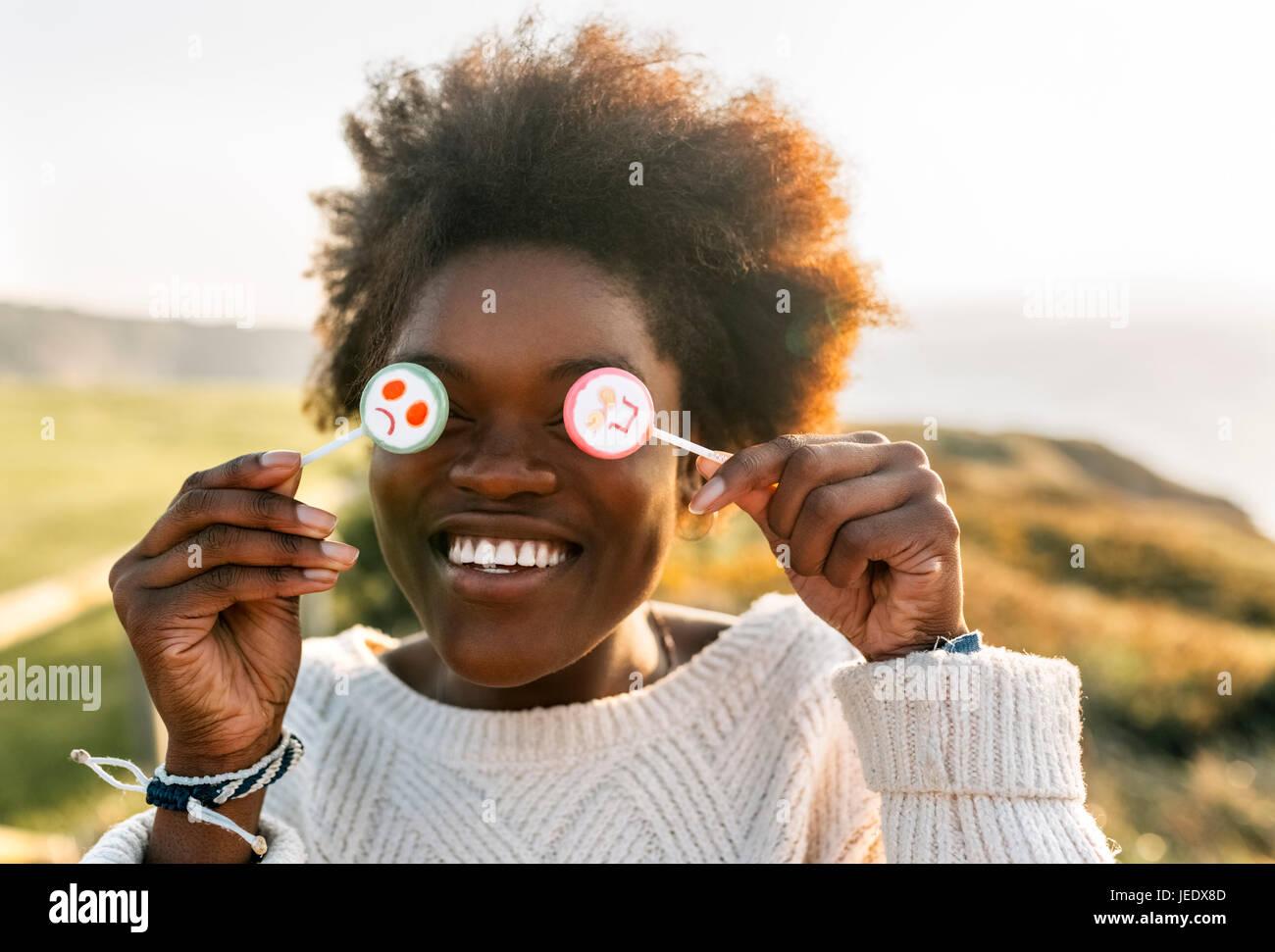 Mujer joven divirtiéndose con lollipops Imagen De Stock