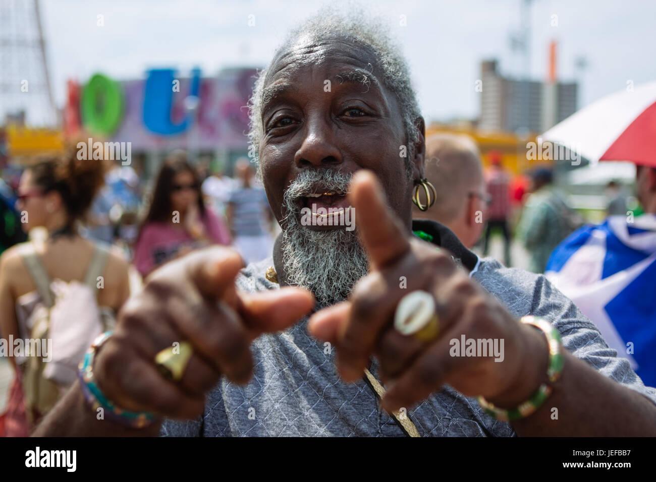 Hombre Negro apuntando a la cámara riendo en Coney Island boardwalk durante el fin de semana de verano, Brooklyn, Imagen De Stock