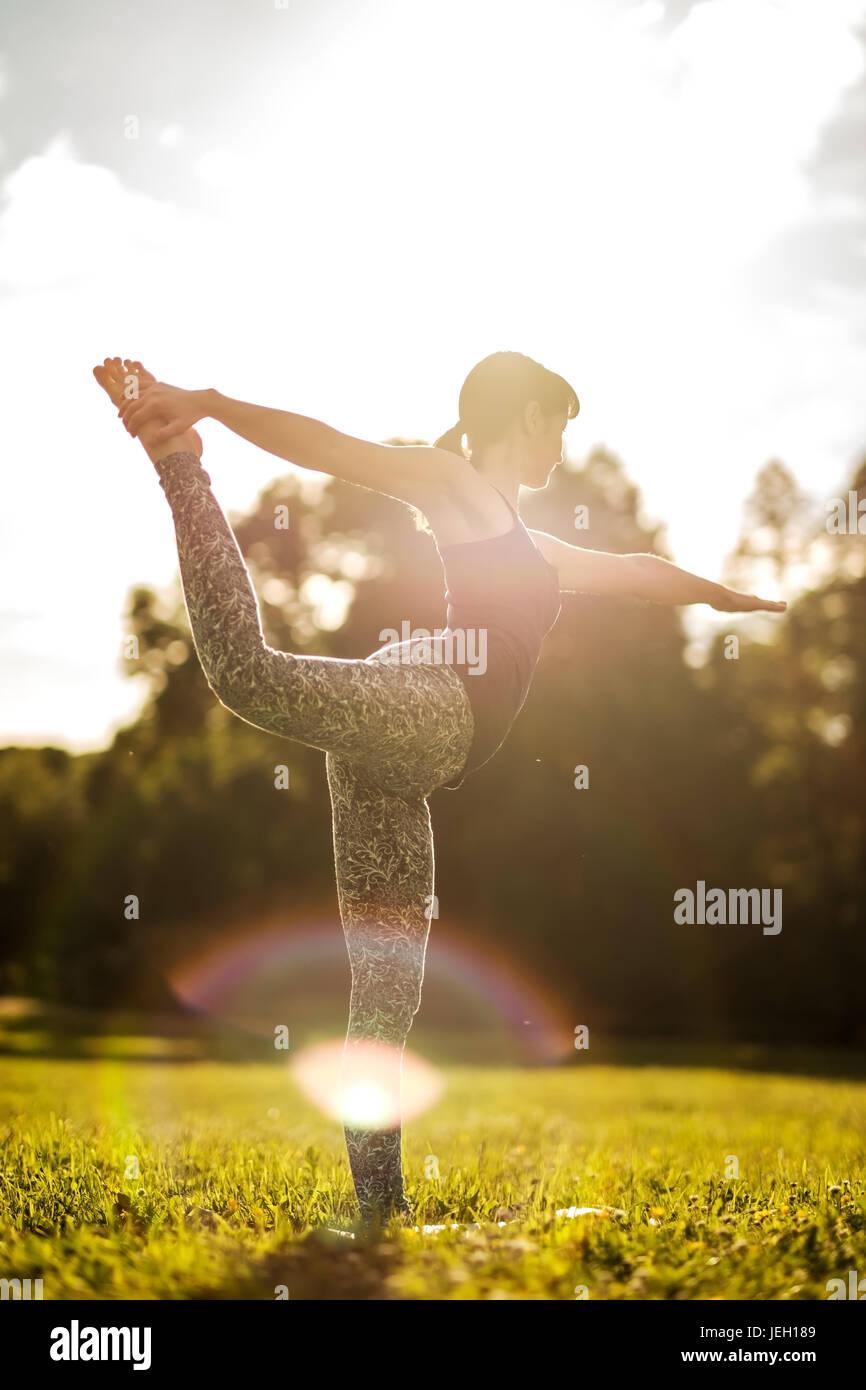 Mujer caucásica en yoga Natarajasana equilibrio permanente. Vista posterior Imagen De Stock