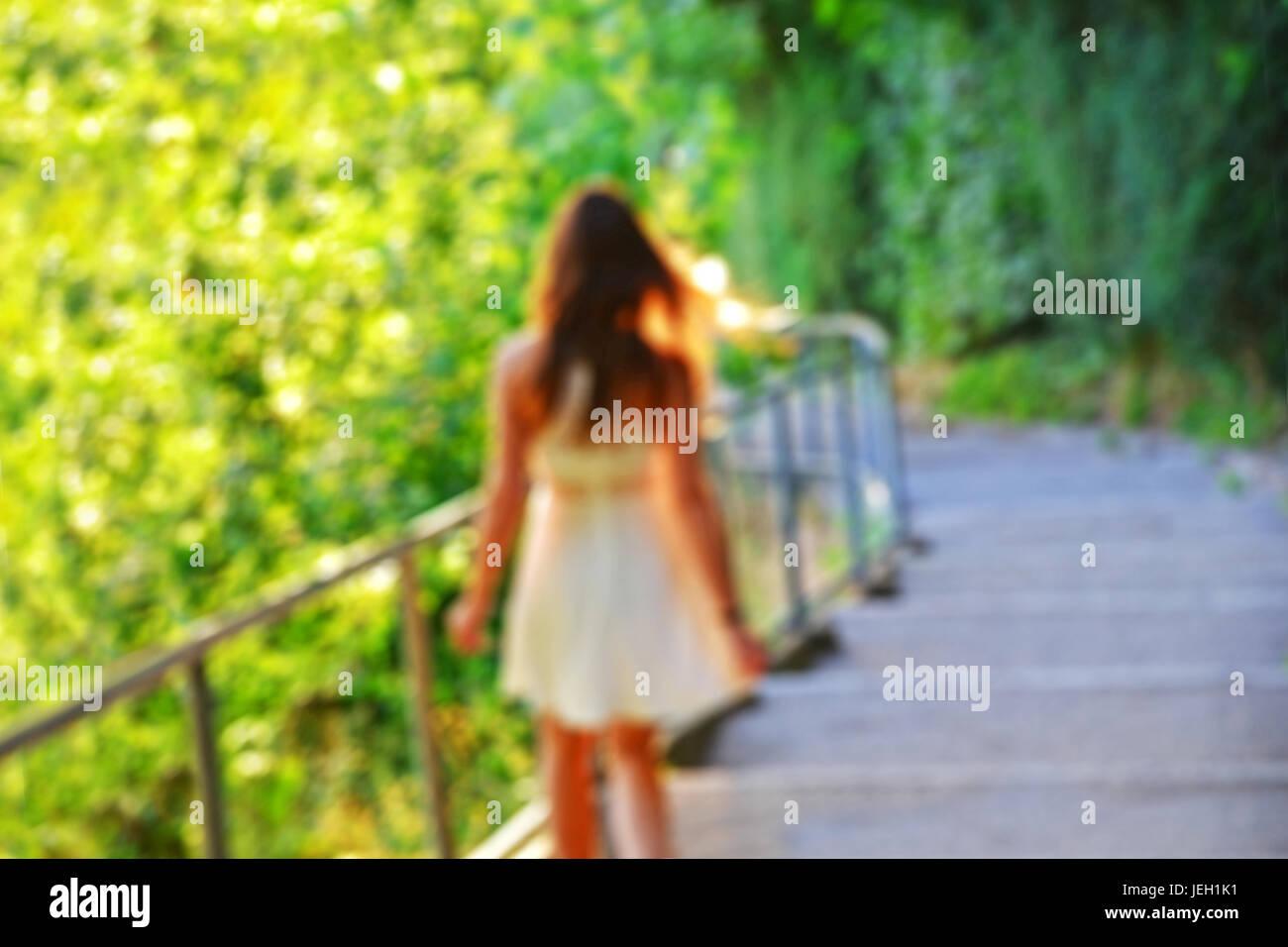Chica en blanco vestido de verano caminando por las escaleras. Imagen borrosa intencionalmente con brillantes antecedentes. Foto de stock