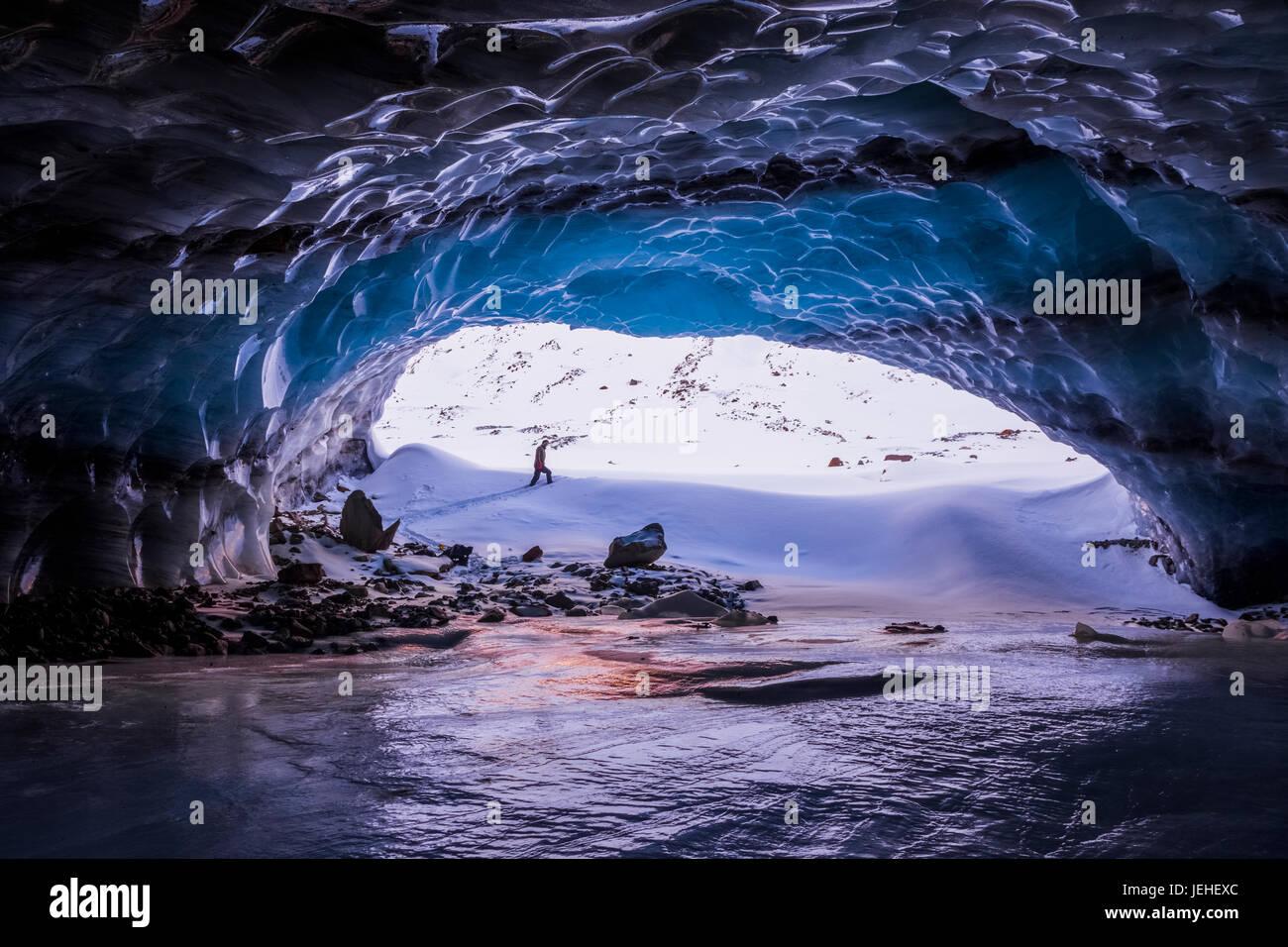 Un hombre está enmarcada por la entrada de una gran cueva de hielo cerca de la terminal de Augustana glaciar en la Cordillera de Alaska en invierno Foto de stock