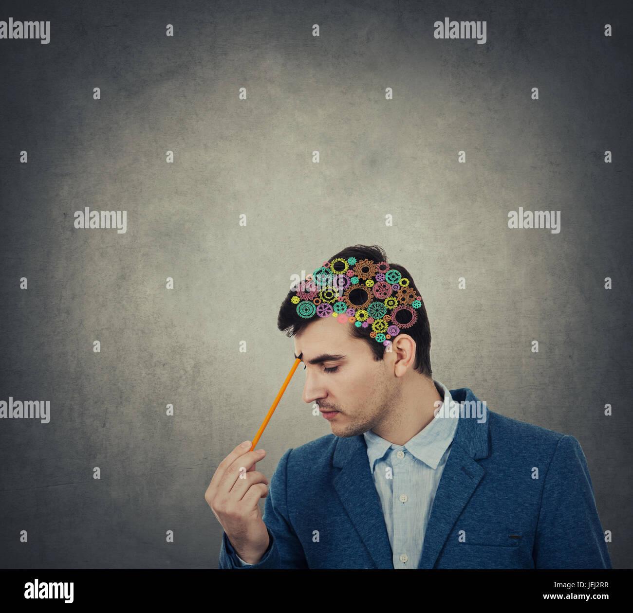 Concepto creativo de un empresario con un lápiz apuntando a su cabeza con un cerebro colorulful realizados Imagen De Stock