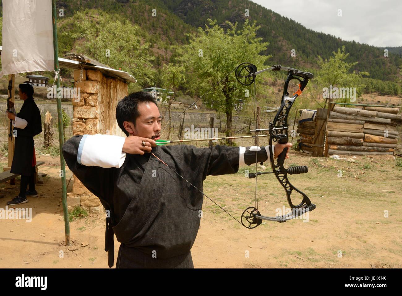 El hombre practicando deporte nacional de tiro con arco, Thimphu, Bután, Asia Imagen De Stock