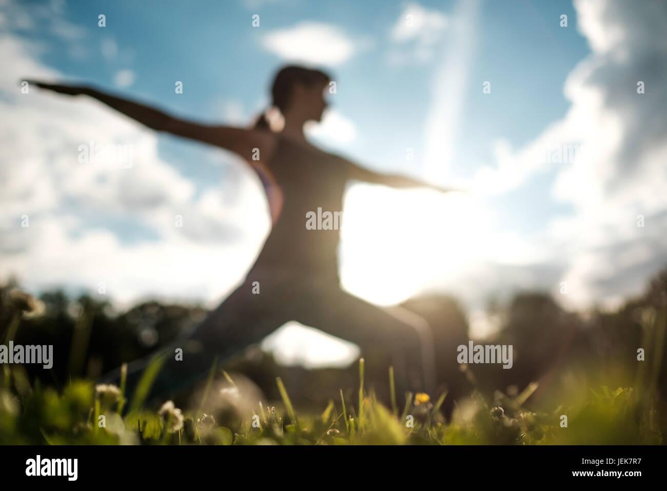 Colocar deportivo mujer caucásica haciendo asana Guerrero Virabhadrasana 2 plantean la postura en la naturaleza. Imagen De Stock