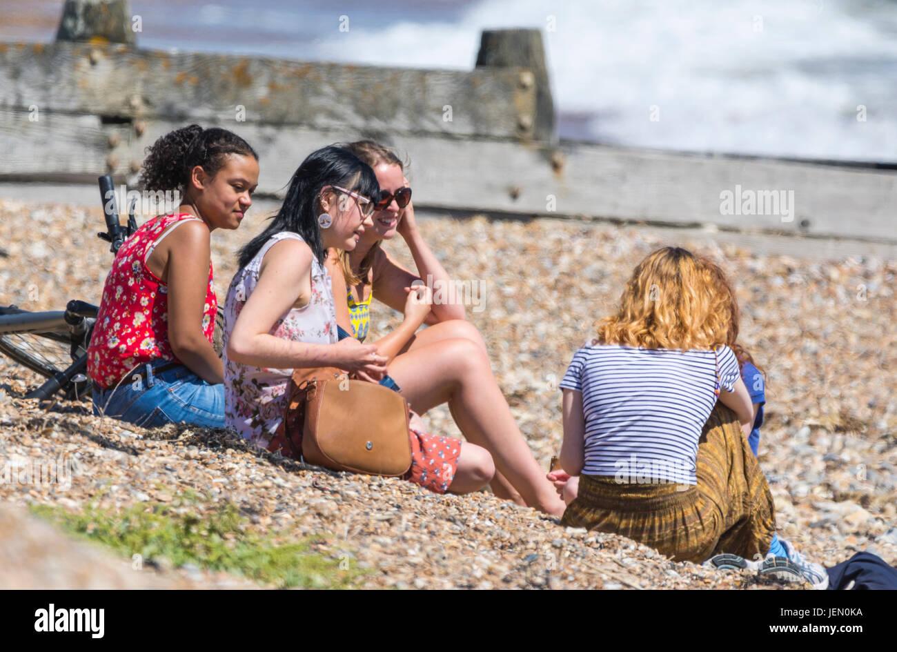 Un grupo de jóvenes de diferentes etnias sentado en una playa disfrutando juntos vistiendo caliente junto al Imagen De Stock