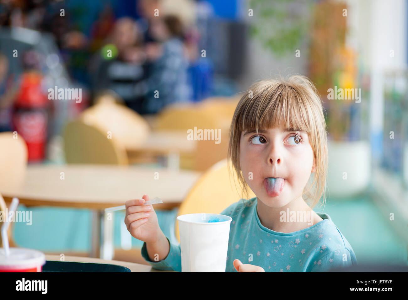 Linda chica rubia pegada o metiendo lengua fuera con azul hielo bebida en brillantemente iluminada con luz natural Imagen De Stock