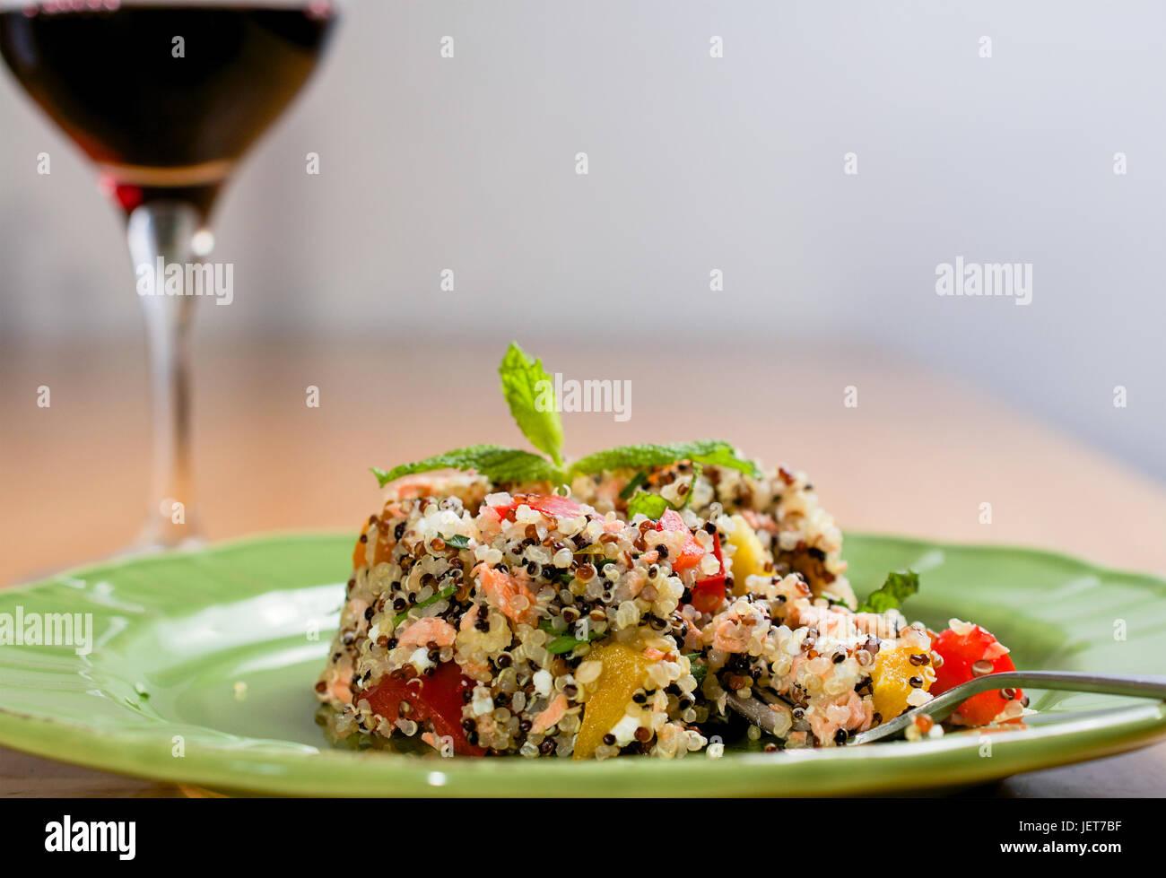 Primer plano sobre la placa verde con quinoa Ensalada tricolor en la mesa de madera, con una copa de vino en el Imagen De Stock