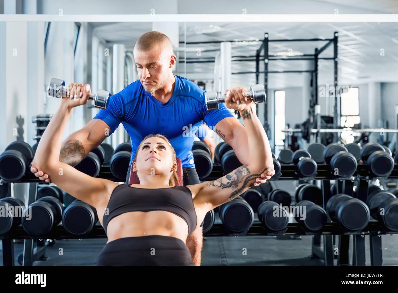 Corrige y entrenador personal mientras que motiva la formación de musculación en el gimnasio. Ayuda profesional Imagen De Stock