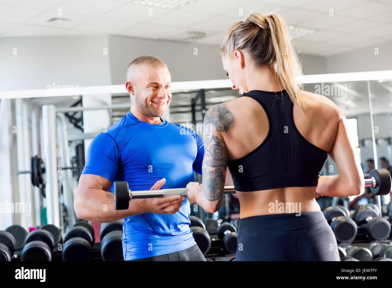 Corrige y entrenador personal mientras que motiva la formación de musculación en el gimnasio. Ayuda profesional durante el entrenamiento. Estilo de vida saludable y el deporte concepto. Foto de stock